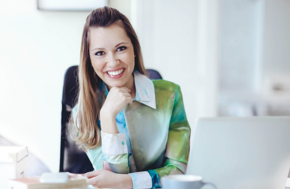 business woman at desk with fist under chin