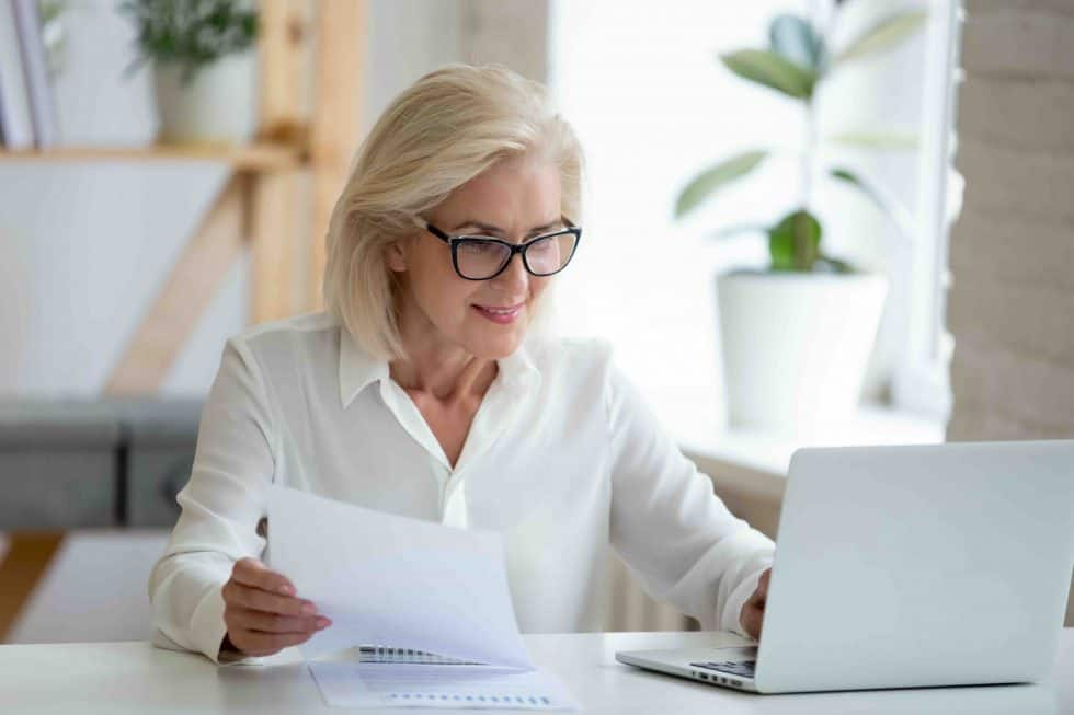 business woman reading letter while on laptop