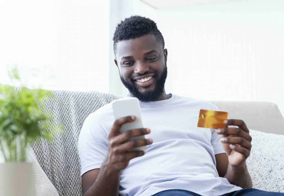 man on sofa activating card on his mobile device
